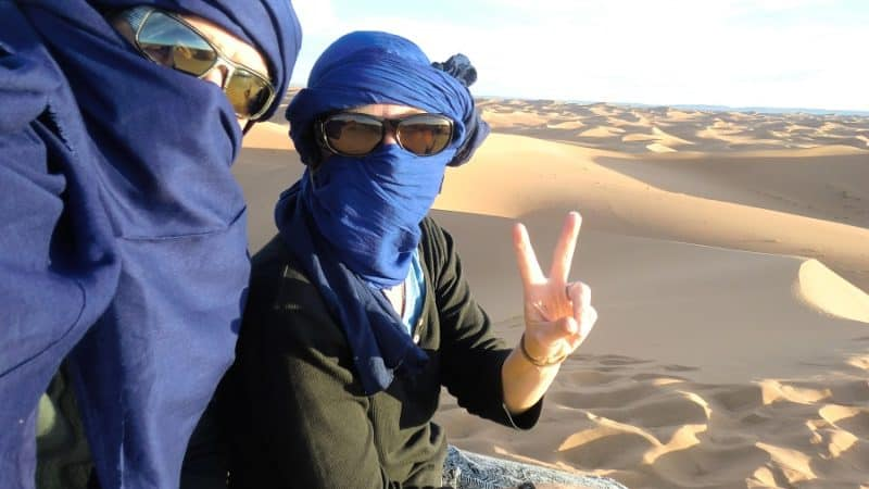 We are shrouded in blue cloth in the Sahara Desert, one of our travel destinations in early retirement.
