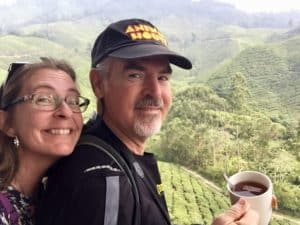 Man and woman have tea at a tea plantation cafe overlooking green fields in Cameron Highlands, Malaysia.
