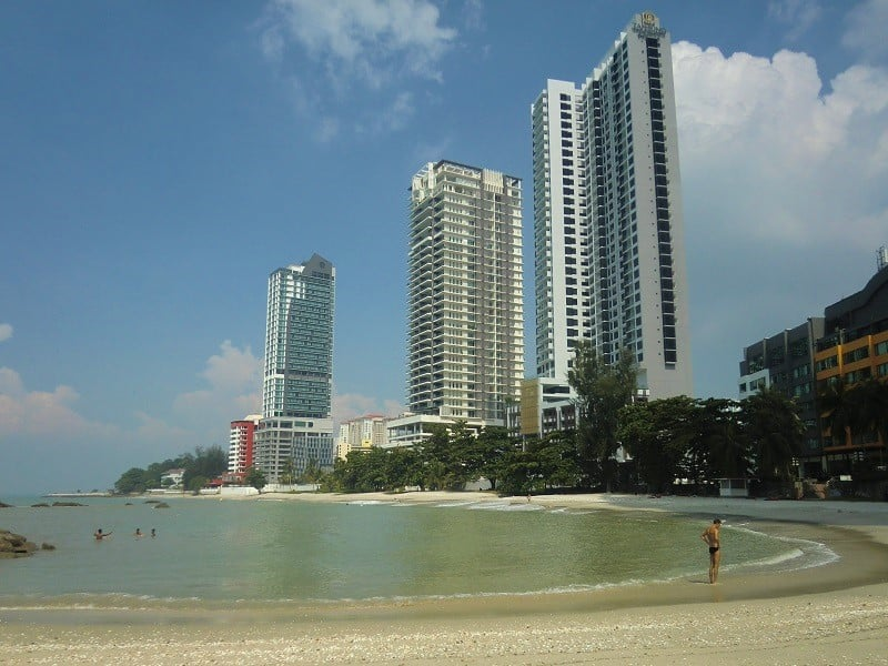 High rise apartment buildings along a sunny beachfront with calm water