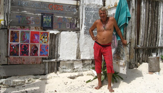 An artist named Tasso von Jena stands in front of his art at his beach hut