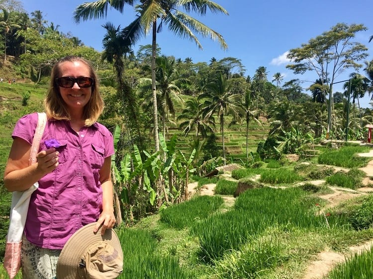 the author holding a purple flower, wearing a purple shirt, against the green of rice terraces
