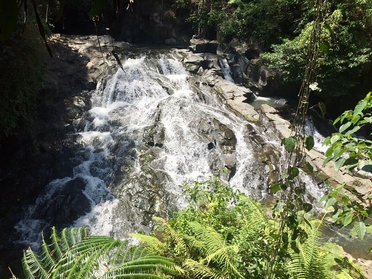 water rushes over rocks at the goa rang reng waterfall - one of the sites near ubud to see while in bali