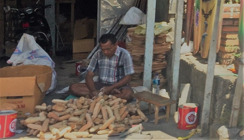 a man sits on the ground carving large wooden penises that will become bottle openers