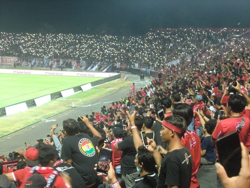 thousands of soccer fans hold up their cell phones at the bali united soccer game - a real life, local detail not in the book or movie eat pray love
