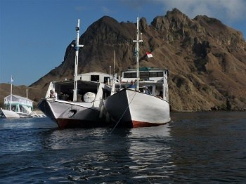 Two tour boats tied together while tourists are ashore to see Komodo dragons.