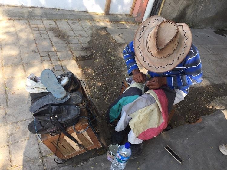 shoe repair man fixes sandals in Labuan Bajo.