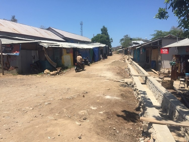 a dirt road with poor homes in Labuan Bajo village