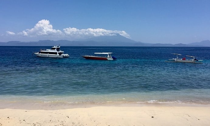 nusa penida tour boats with a volcano in the background