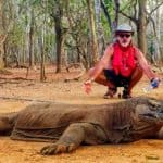 A man squats near a Komodo dragon with his arms outstretched