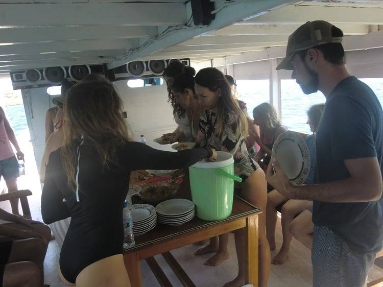 people get food in the dining area of the cheap komodo dragon tour boat
