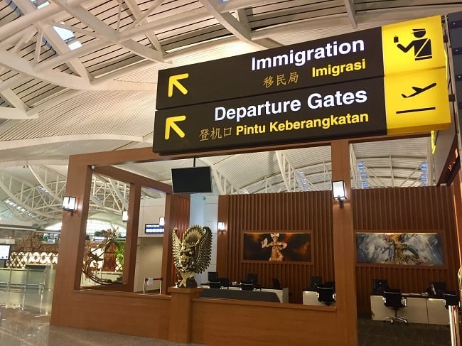 a sign reads, 'immigration' and 'departure gates' inside an airport, after we were asked to show proof of onward travel
