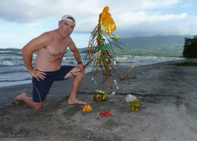 tedly kneels on the beach by his trashy christmas tree in nicaragua