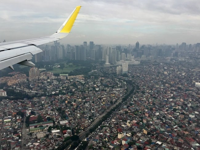 the wing tip of cebu pacific flying into a smoggy manila airport