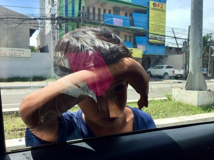 a child puts his head against a car window, begging for money in cebu city, named 'the most typical place in the world'