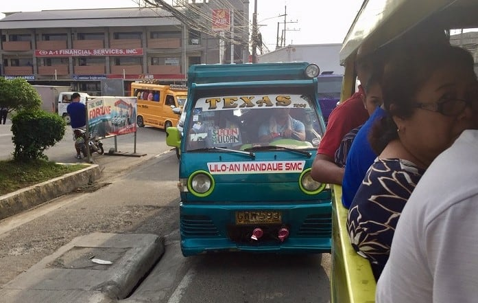 three jeepneys filled with people in cebu city traffic