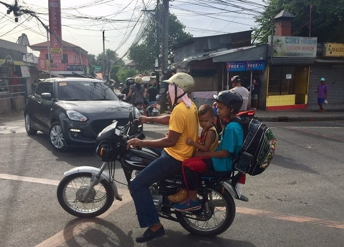 a young man on a motorcycle with two young boys on the back in cebu city traffic