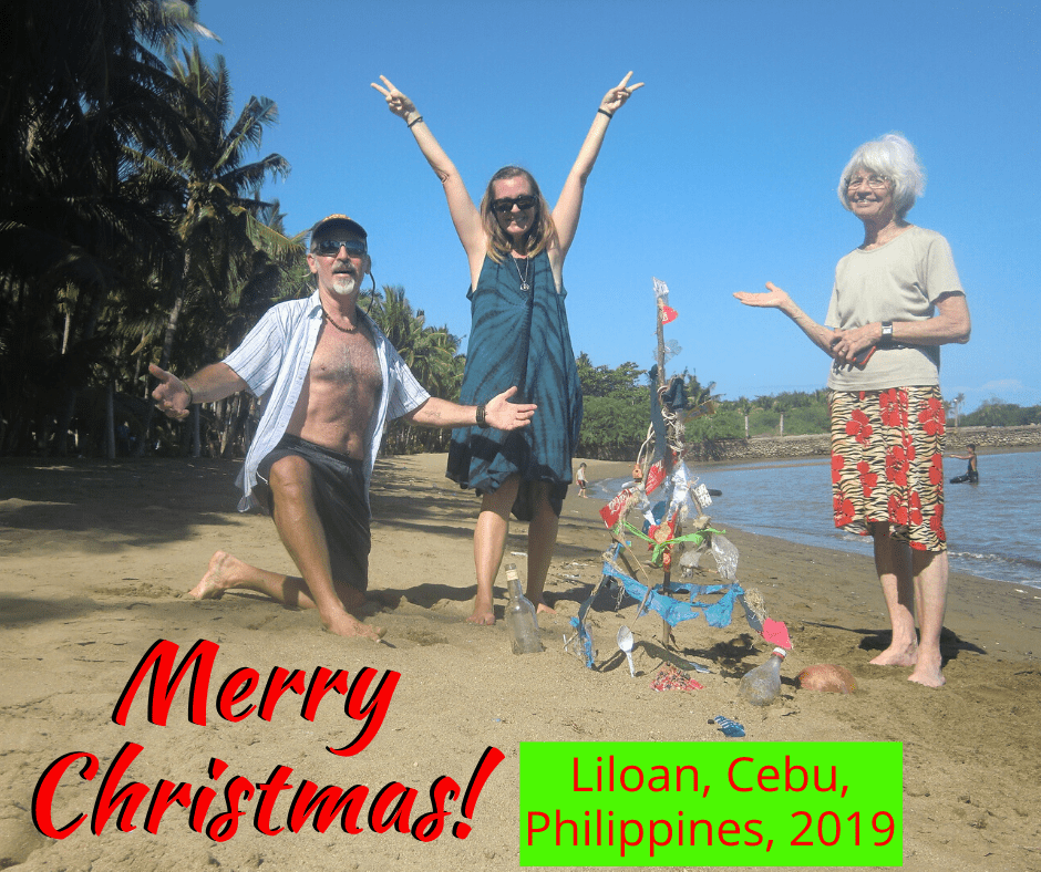 "me, tedly, mom diane stand around the trashy christmas tree on the beach with the words ""merry christmas, liloan, cebu, 2019"""