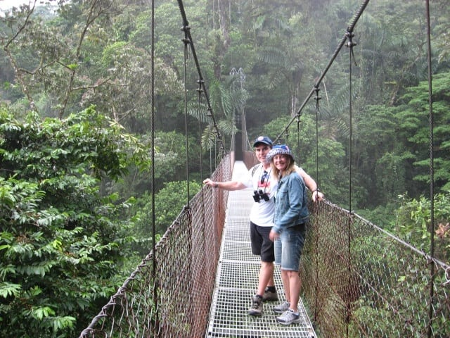 couple on a bridge in the rain forest in costa rica