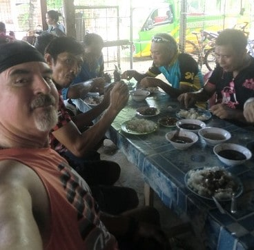 men eating at table after adventure cycling