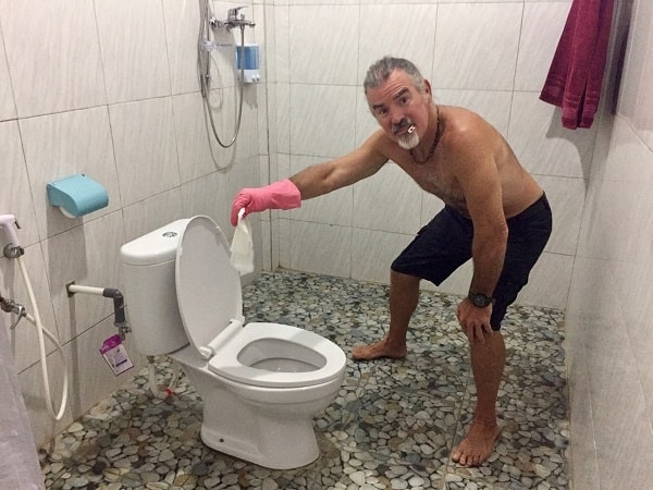 man with rubber gloves holding disinfectant wipe over a toilet as part of his travel cleaning kit