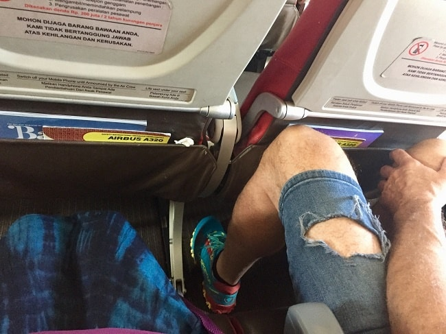 batik air is short on leg room for tall people as seen in this photo of a man about 6 feet tall sitting in a seat