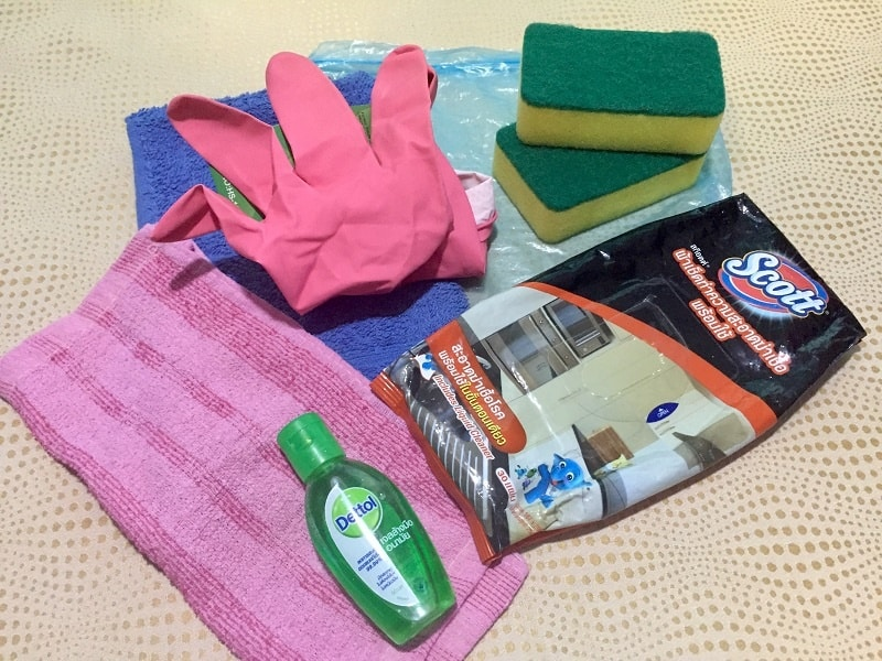 travel cleaning kit items laid out: rubber gloves, scrubbie sponges, disinfectant wipes, wash cloth, small towel, liquid soap, hand sanitzer, plastic bag