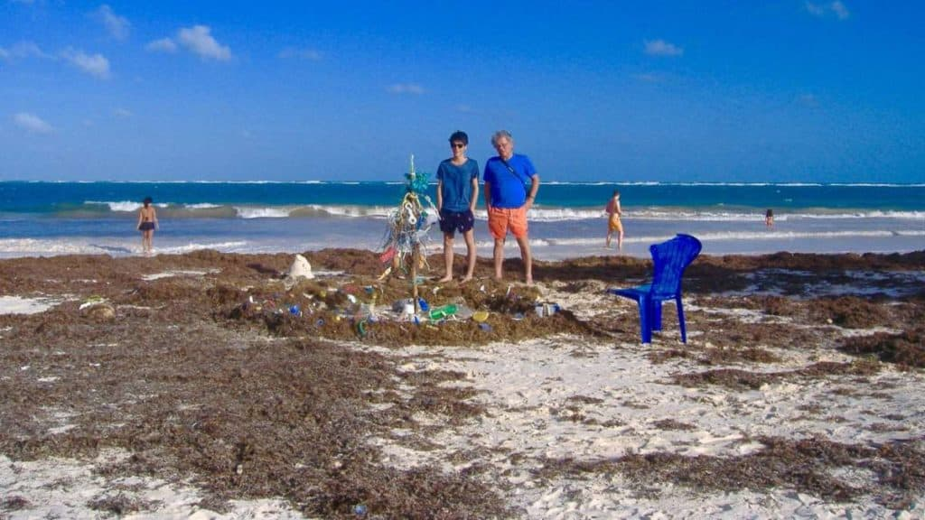 man and boy stand on the beach near the water and look at an art installation made of plastic trash from the beach