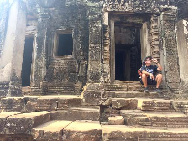 Southeast Asian cheap beer report -- man sitting at Angor Wat drinking beer can