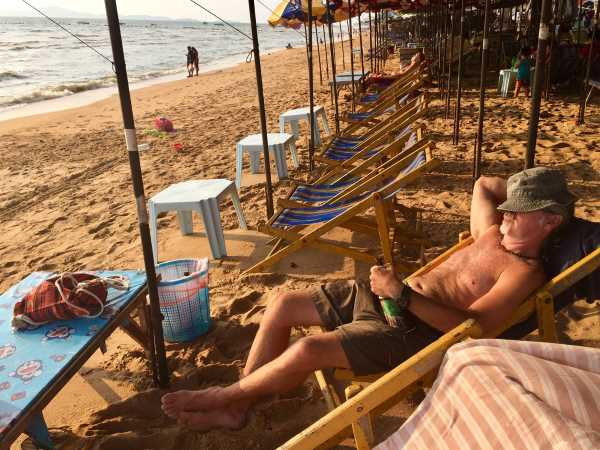 Southeast Asian cheap beer report - man with liter of beer sleeping on the beach