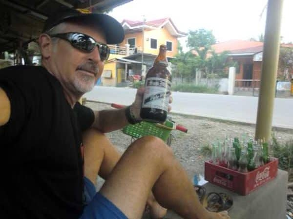 Southeast Asia cheap beer report - man smiles with liter of San Miguel beer.