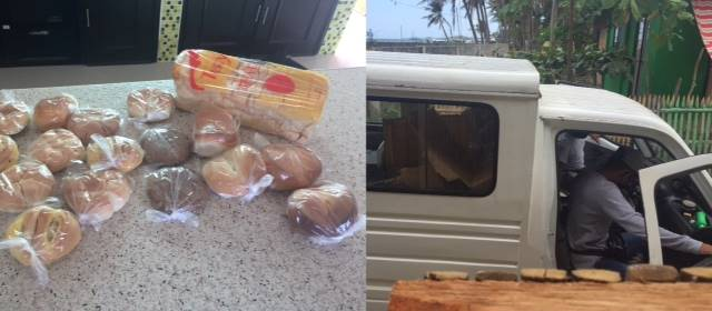 several rolls and pastries and a loaf of bread on a counter; the bread truck in the road