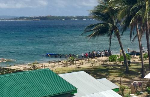 several men on the beach pull in a huge net from the sea on philippine quarantine day 12