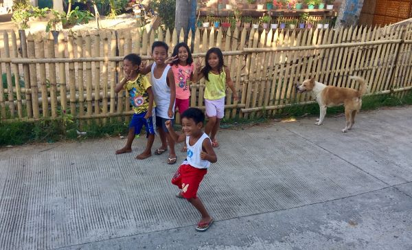 Neighborhood kids give the camera peace signs and smiles on philippine quarantine day 12.