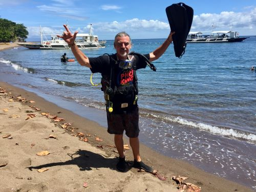 man gets ready to dive at dauin marine sanctuary