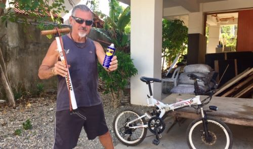 tedly holds up oil can and bike pump in front of his pandemic bicycle