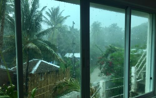 welcome to rainy season: view out wet window to rain and clouds
