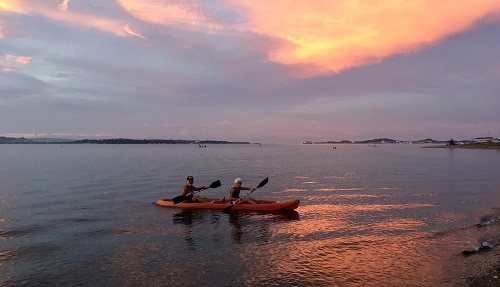 mortality reminders: 57-year-old man and his 81-year-old mother kayaking at sunset