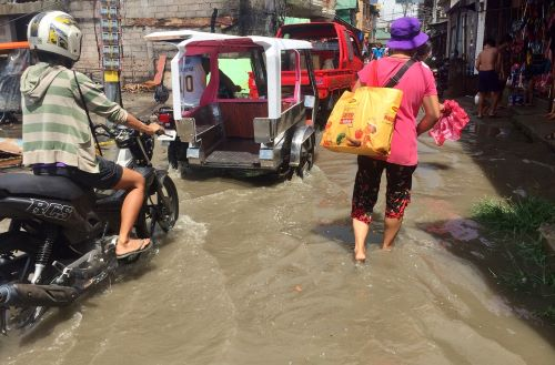 a truck, a trike, a motorbike, and a woman all wade through rain water on a street in caticlan