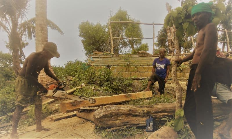Ati workers use chainsaw on a rebuilding project