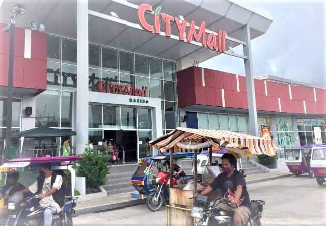 City Mall entrance in Kalibo with several people in trikes (taxis) wearing masks.