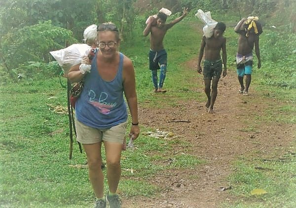 Ellen carries a sack of snacks up the mountain, followed by three Ati men with heavy sacks of building supplies on their shoulders.