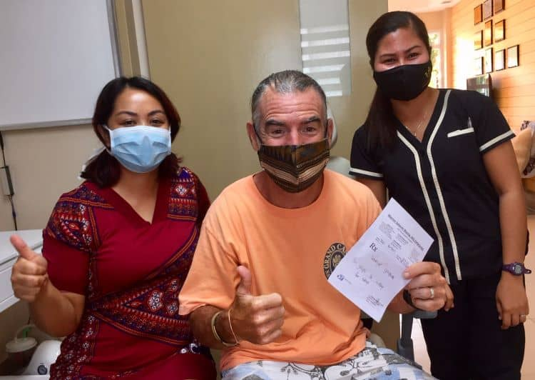 Tedly smiles with doctor and assistant who pulled tonsil stones out of his throat.