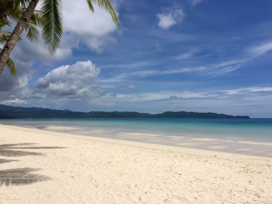 A stunning view of powdery white sand, blue sea and sky, with another island in the background.