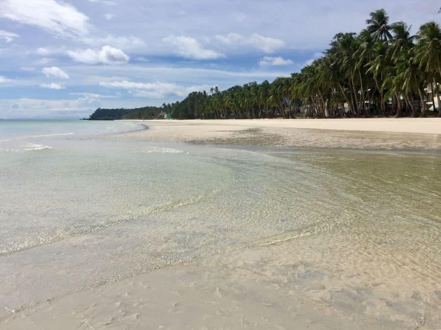 Palm trees, crystal clear water, white sand on White Sand Beach on Boracay during the pandemic.