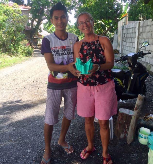 Gido and Ellen smile at the camera, holding a planter pot.