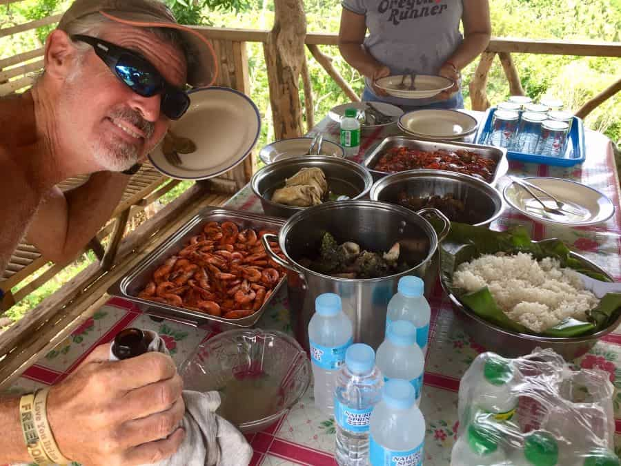 a pile of food in pans on a table in a shelter with jungle and sea views at Tuhaw Hills in mainland Malay
