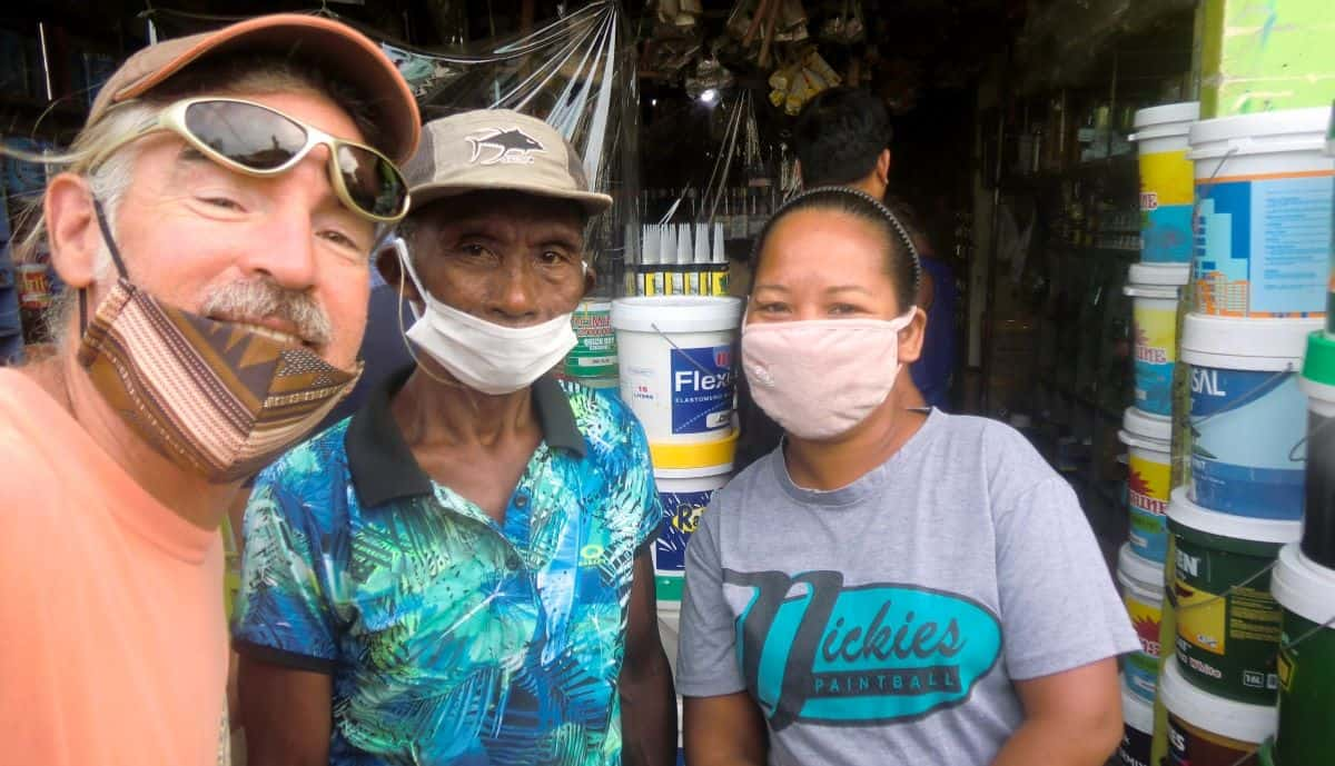 Tedly, left, goes supply shopping with Ati chief, center, and secretary, right, in the town of Caticlan, Aklan Province, Panay Island, in the Philippines, during a pandemic.