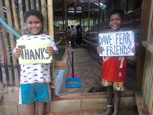 "Two smiling Ati children hold signs that say, ""Thanks Dave Fear + Friends"" at the entry of the henhouse where we got eggs now!"