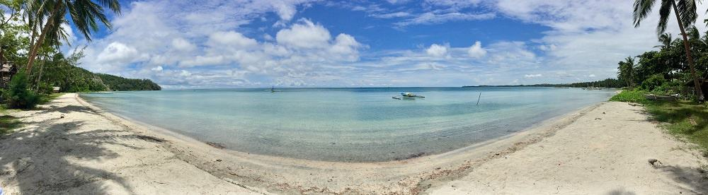 Jawili Beach in a panorama shot on a clear day with blue skies and puffy white clouds.
