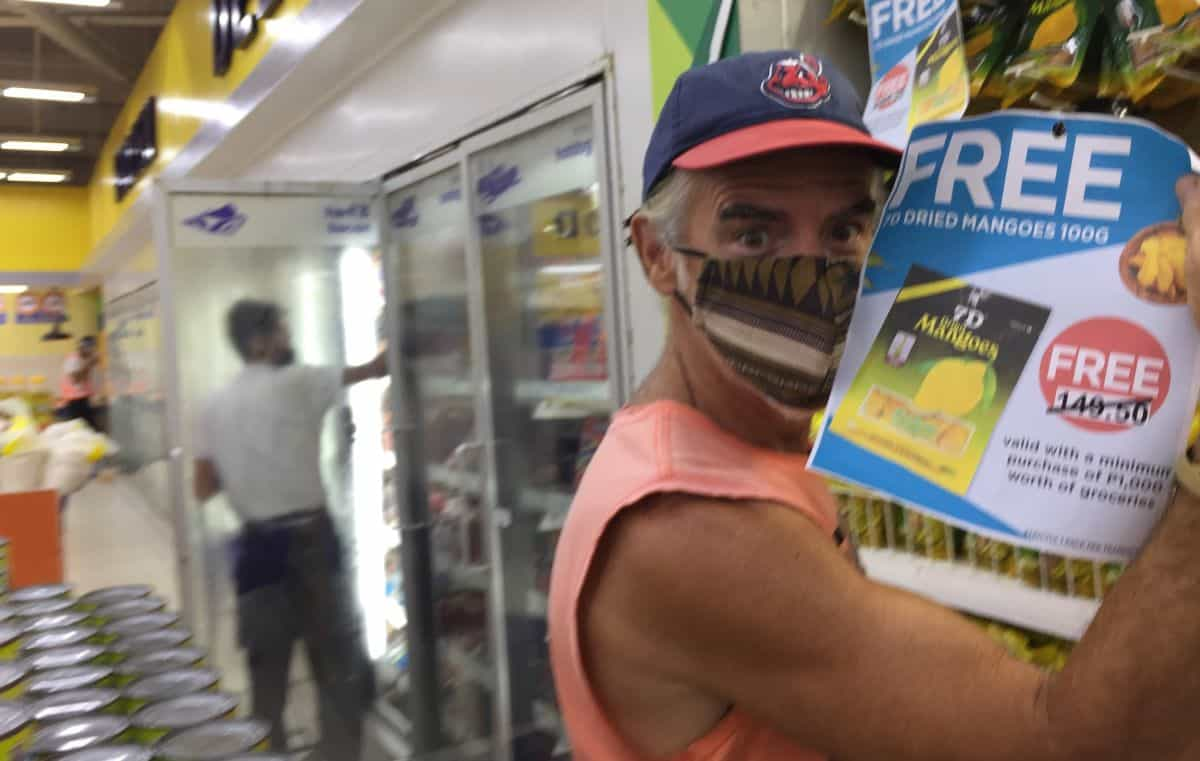 tedly holds up the free dried mangoes sign after he gets the beer deal in a philippine grocery store on boracay island during a pandemic